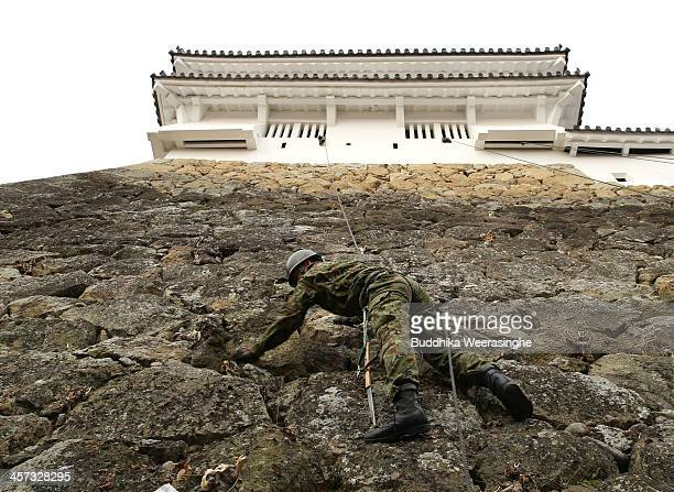 A member of the Japanese Self Defense Force cleans the Himeji Castle wall on December 17 2013 in Himeji Japan Every year JSDF is assigned to clean...