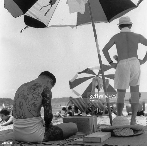 A member of the Japanese underworld covered in the customary tattoos of the Japanese gangster preparing his fishing gear on the beach Some of the...