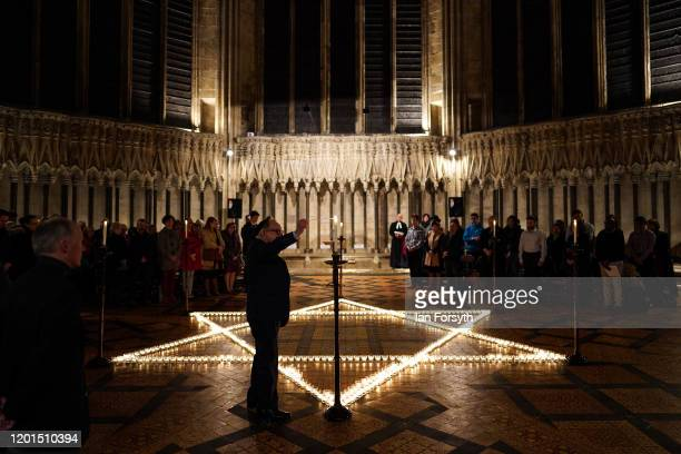 Member of the Jewish community lights a candle alongside 600 others that are set out as a Star of David on the floor of the Chapter House of York...