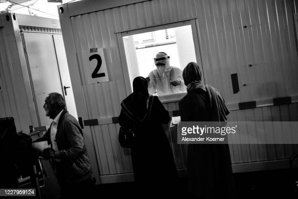 Member of the Johanniter, tests a traveller arriving from abroad wait to be at a Covid-19 testing station set up at Hanover-Langenhagen Airport on...