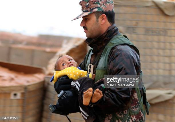 TOPSHOT A member of the Jordanian armed forces carries a toddler from the informal Rukban camp which lies in noman'sland off the border between Syria...