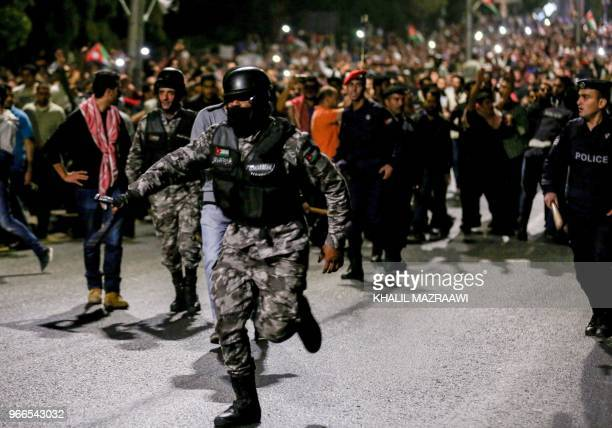 A member of the Jordanian gendarmerie runs as riot police stand on guard before protesters during a demonstration outside the Prime Minister's office...