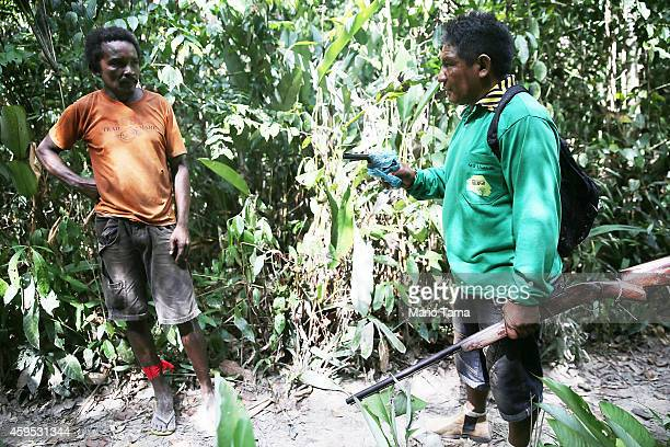 Member of the Ka'apor indigenous tribe holds a rifle just confiscated from a man suspected of setting an illegal fire for logging on their protected...