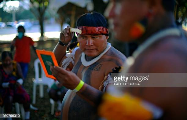 TOPSHOT A member of the Kalapalo tribe applies body paint on his hair at the Acampamento Terra Livre during the Indigenous National Mobilization week...
