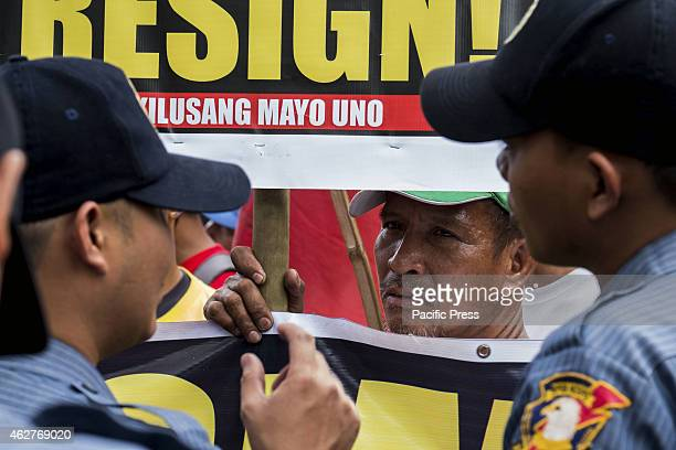 MANILA PHILIPPINES MANILA PHILIPPINES A member of the Kilusang Mayo Uno listens to the conversation of the Police officers who serve as barricades...