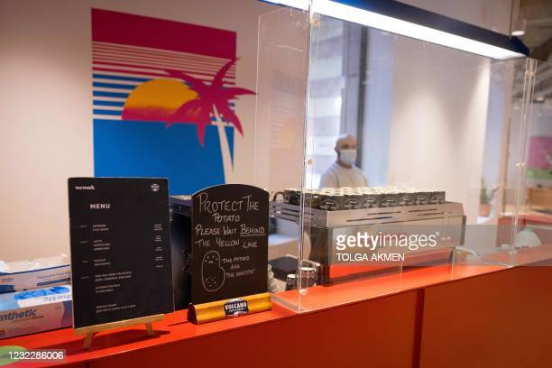 Member of the kitchen staff wears a facemask as he works behind a transparent shield at the WeWork, coworking and office space in the City of London,...