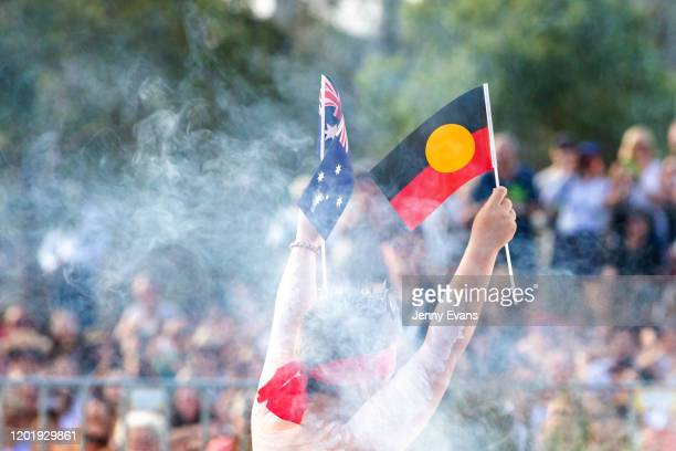 Member of the Koomurri dancers holds up an Indigenous and Australian flag during the WugulOra Morning Ceremony on Australia Day at Walumil Lawns,...