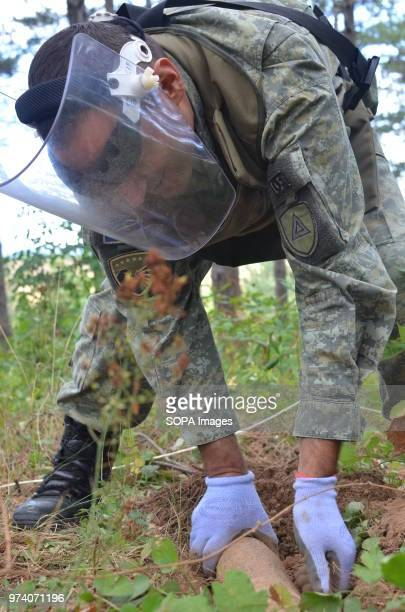 A member of the Kosovo Security Force Emergency Ordinance Disposal team removes an unexploded shell from Freedom Park near Prizren southern Kosovo...