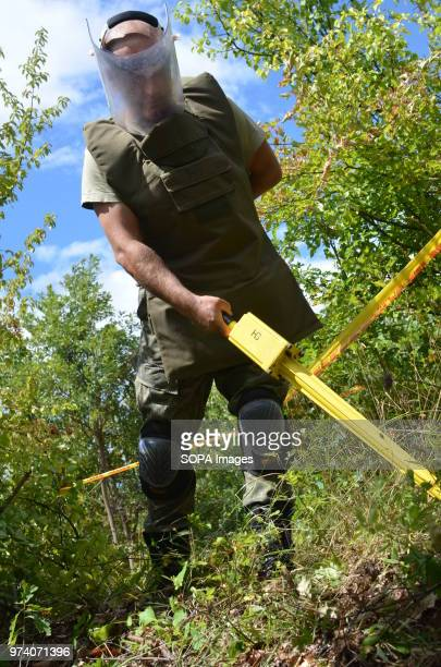 A member of the Kosovo Security Force Emergency Ordinance Disposal team scans for the ground for unexploded shells and mines in Freedom Park near...
