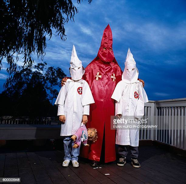 Member of the Ku Klux Klan and his two children wearing traditional Klan clothes