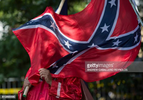 A member of the Ku Klux Klan holds a Confederate flag over his face during a rally calling for the protection of Southern Confederate monuments in...