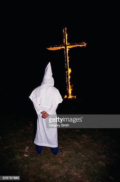 A member of the Ku Klux Klan watches as a cross burns in Hico Texas The public was invited to the rally and nearly 300 people attended