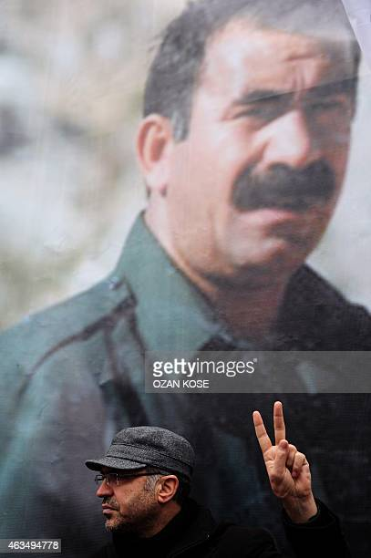 A member of the Kurdish community flashes a victory sign in front of a banner of convicted Kurdistan Worker's Party leader Abdullah Ocalan during a...