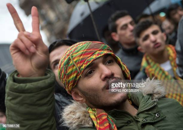 A member of the Kurdish community in Germany flahes the sign of victory during a demonstration on January 18 2018 in Frankfurt am Main to protest...