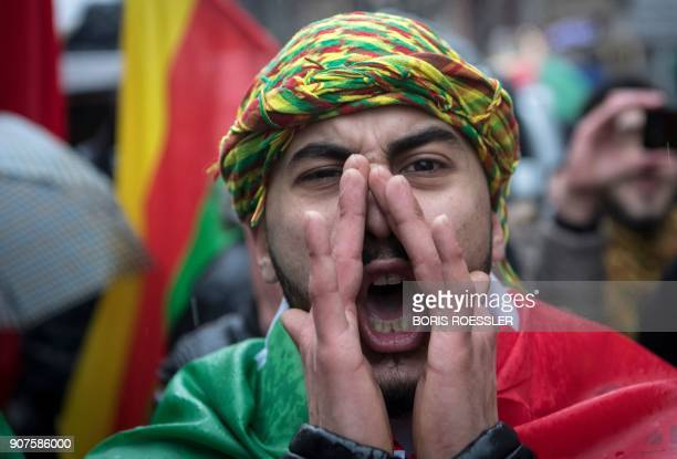 A member of the Kurdish community in Germany shouts slogans the sign of victory during a demonstration on January 18 2018 in Frankfurt am Main to...