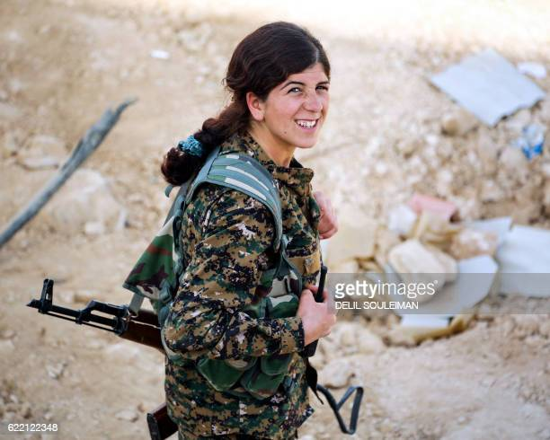 A member of the Kurdish female Women's Protection Units smiles as she carries a Kalashnikov assault rifle in the Syrian village of Mazraat Khaled...