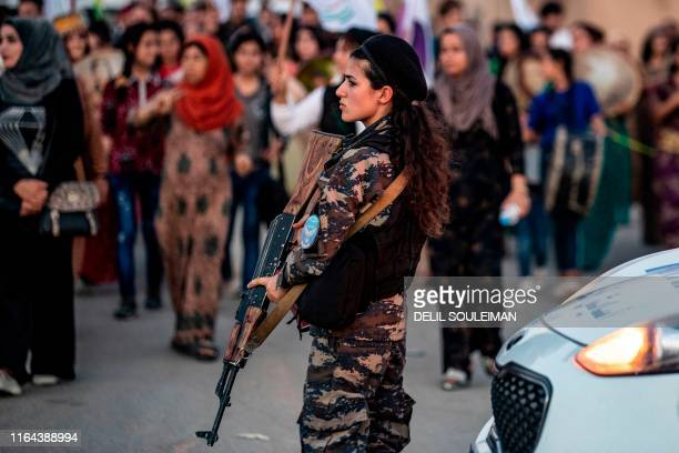 Member of the Kurdish Internal Security Police Force of Asayesh stands guard as Syrian Kurdish demonstrate against Turkish threats to invade the...