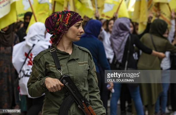 Member of the Kurdish internal security services known as Asayish stands guard during a demonstration by Syrian Kurds against the Turkish assault on...