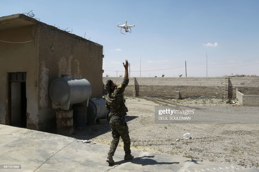 A member of the Kurdish People's Protection Units (YPG) flies a drone at a position in the al-Dariya neigbourhood of the Syrian city of Raqa, on June 18, 2017, during an offensive by US-backed fighters to retake the Islamic State (IS) group bastion. /