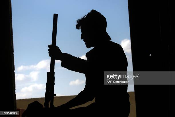 Member of the Kurdish People's Protection Units holds a weapon in the Syrian city of Raqa's eastern al-Sinaa district, on June 21 during an offensive...
