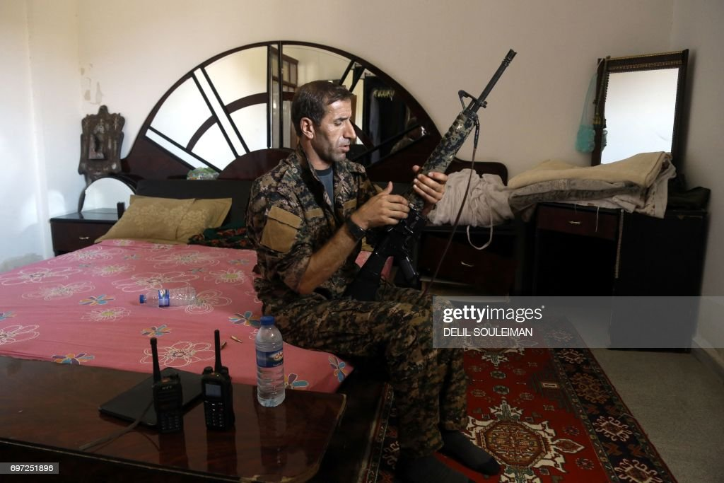 TOPSHOT - A member of the Kurdish People's Protection Units (YPG) sits in a bedroom as he holds a position in the al-Dariya neigbourhood of the Syrian city of Raqa, on June 18, 2017, during an offensive by US-backed fighters to retake the Islamic State (IS) group bastion. /