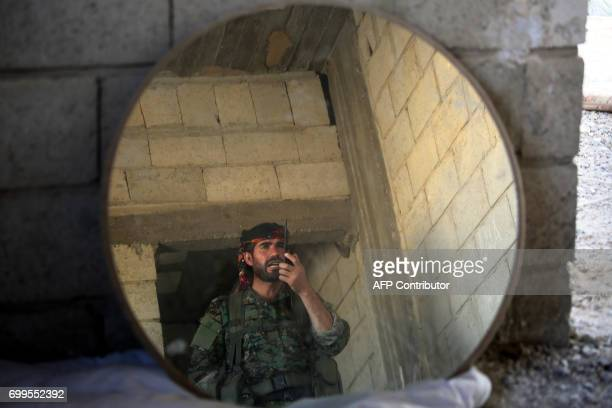 TOPSHOT A member of the Kurdish People's Protection Units speaks on a walkie talkie in the Syrian city of Raqa's eastern alSinaa district on June 21...