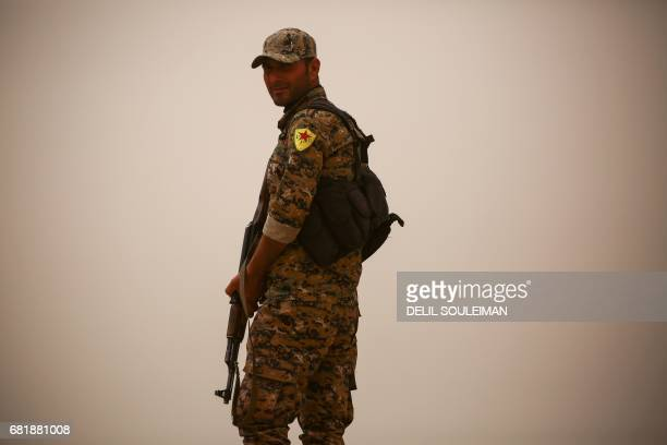 A member of the Kurdish People's Protection Units stands guard carrying a Kalashnikov assault rifle in the town of alKaramah 26 kms from the Islamic...