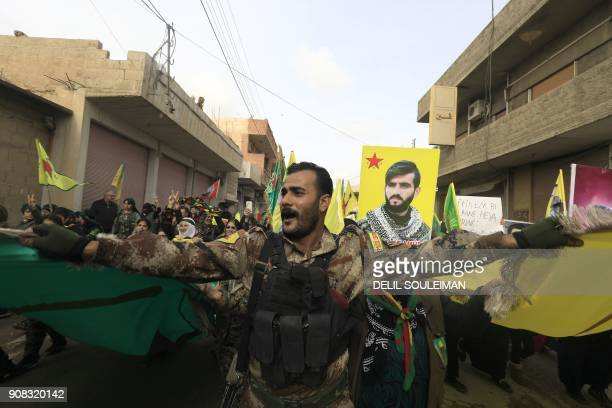 Member of the Kurdish People's Protection Units takes part in a demonstration alongside Syrian-Kurds in the town of Amuda, some 30 kilometres west of...