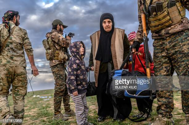 TOPSHOT A member of the Kurdishled Syrian Democratic Forces helps a woman after she left the Islamic State group's last holdout of Baghouz in Syria's...