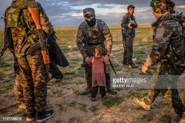 Member of the Kurdish-led Syrian Democratic Forces holds a toddler during a security check of her and her mother after they left the IS group's last...