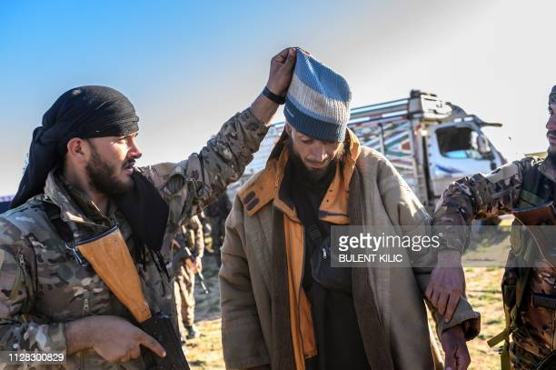 A member of the Kurdishled Syrian Democratic Forces raises a hood on the head of a reported Bosnian man who is suspected of being an Islamic State...