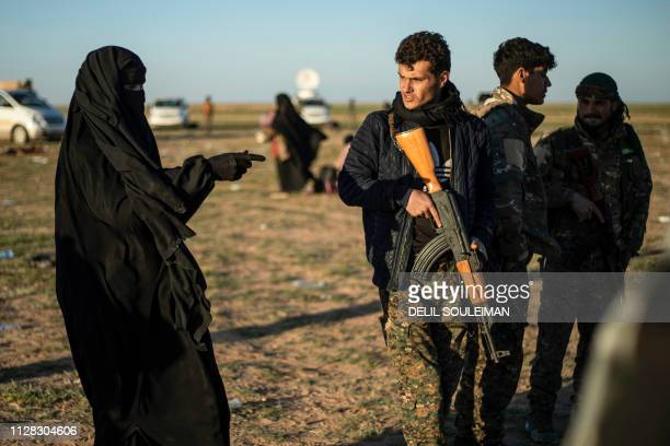 A member of the Kurdishled Syrian Democratic Forces speaks with a woman leaving the Islamic State group's last holdout of Baghouz in the eastern...