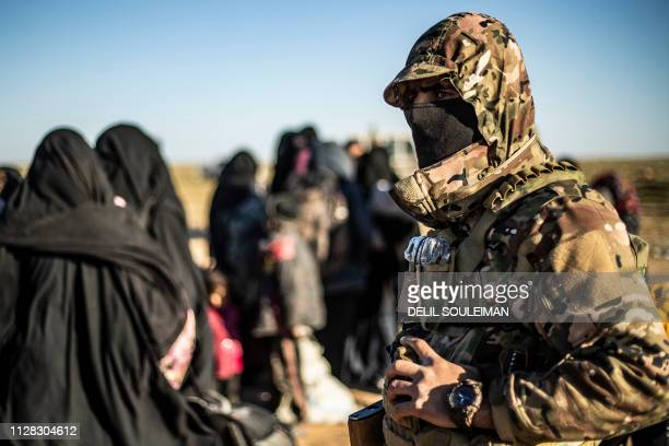 A member of the Kurdishled Syrian Democratic Forces stands by as women and children walk while leaving the Islamic State group's last holdout of...