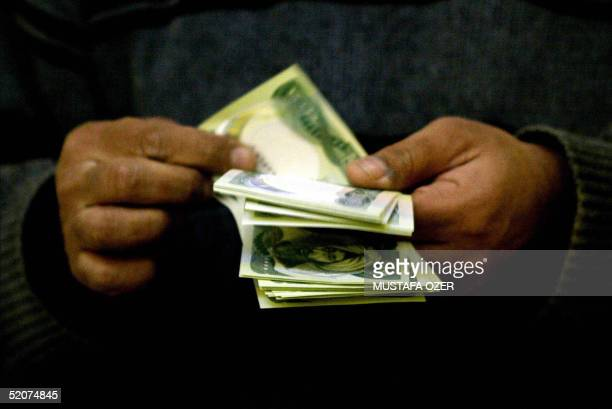 A member of the Kurdistan Communist Party counts money after receiving his donation in Arbil northern Iraq 28 January 2005 Campaigning by candidates...