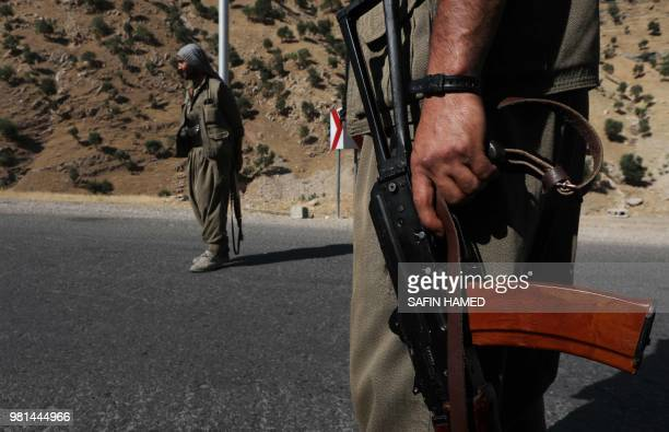 A member of the Kurdistan Workers' Party carries an automatic rifle on a road in the Qandil Mountains the PKK headquarters in northern Iraq on June...