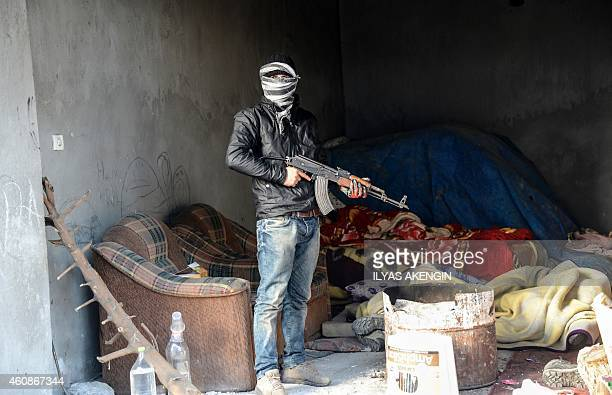 A member of the Kurdistan Worker's Party stands with an AK47 in the town of Cizre Sirnak Province in southeastern Turkey on December 28 2014 Turkish...