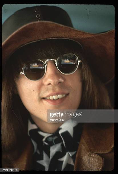 A member of the latesixties hard rock band Steppenwolf Jerry Edmonton rides in a car He wears a star print shirt and leather hat and jacket...