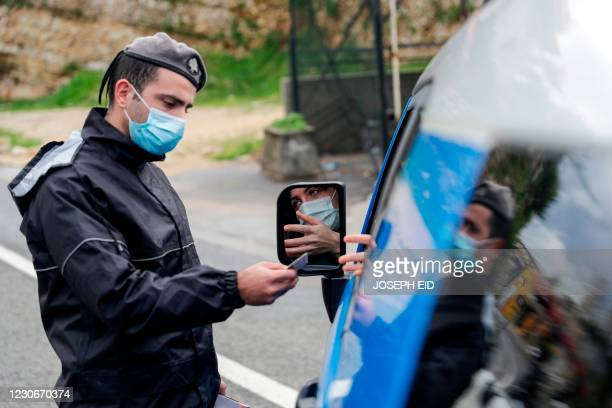Member of the Lebanese security forces checks a citizen's documents at a COVID-19 checkpoint near the coastal town of Safra on the Tripoli-Beirut...
