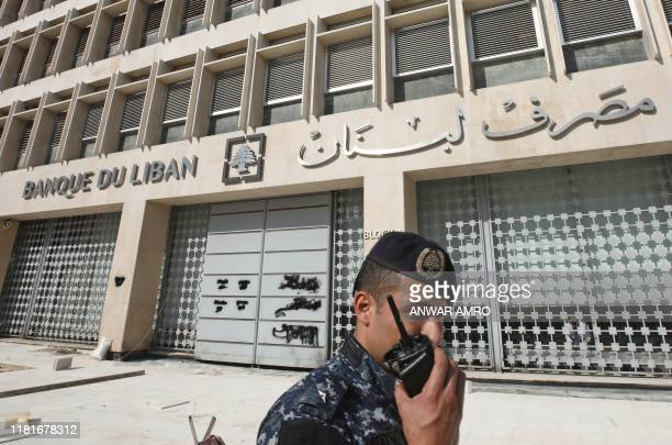 Member of the Lebanese security forces stands at the entrance of the Central Bank after anti-government protesters broke down a construction barrier...