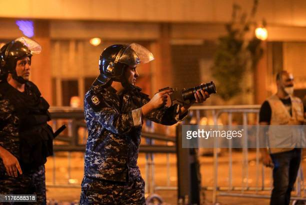 A member of the Lebanese security forces uses a tear gas grenade launcher amidst clashes during a mass protest at Riad alSolh Square in the centre of...
