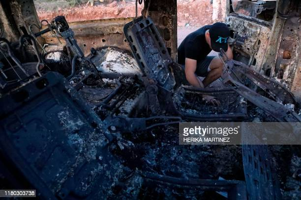 A member of the Lebaron family looks at the burned car where part of the nine murdered members of the family were killed and burned during an ambush...
