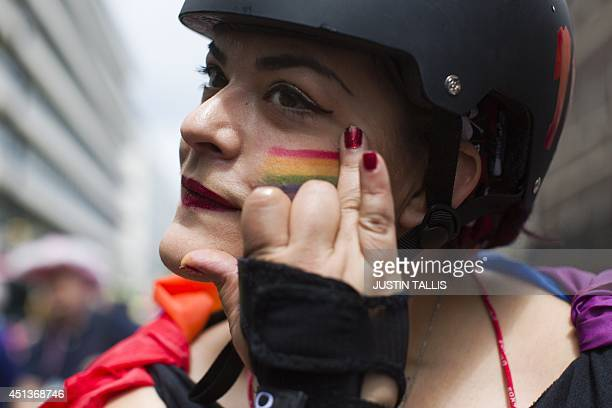A member of the Lesbian Gay Bisexual and Transgender community rubs glitter on her cheek during the annual Pride Parade in London on June 28 2014 AFP...