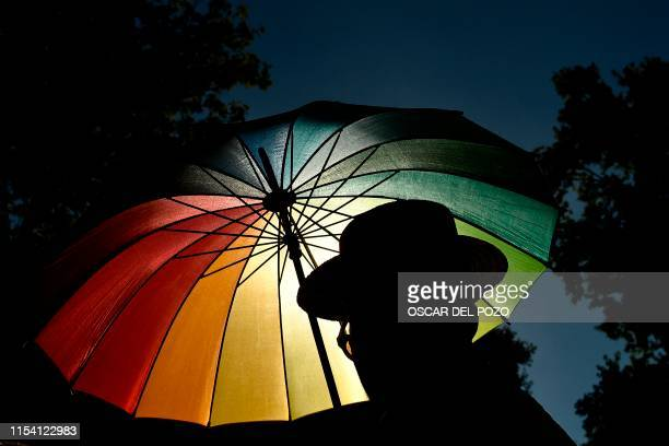 TOPSHOT A member of the Lesbian Gay Bisexual Transgender Intersex and Queer community holds an umbrella decorated with the colors of the rainbow flag...