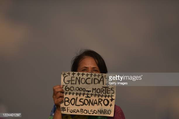 A member of the 'Levante de Mulheres' group holds a sign that reads Bolsonaro Genocide 60 thousand dead in a rally against President Jair Bolsonaro...