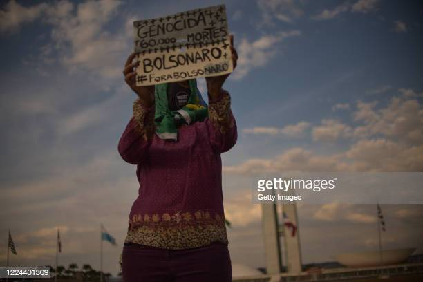 """Member of the 'Levante de Mulheres' group holds a sign that reads """"Bolsonaro Genocide. 60 thousand dead"""" in a rally against President Jair Bolsonaro..."""