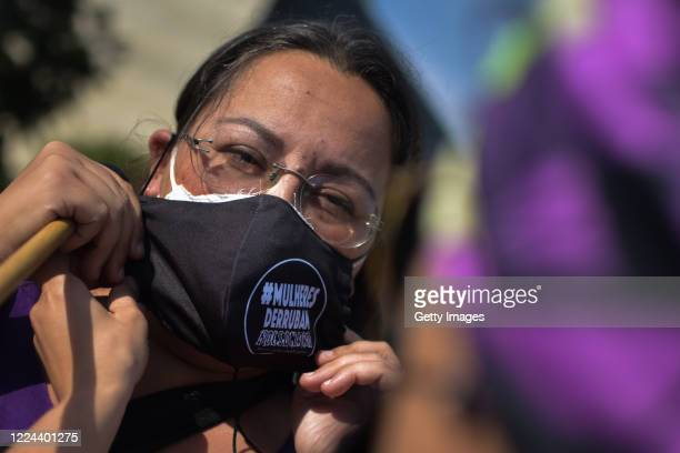 """Member of the 'Levante de Mulheres' group puts on a face mask that reads """"Women bring down Bolsonaro"""" during a rally against President Jair Bolsonaro..."""
