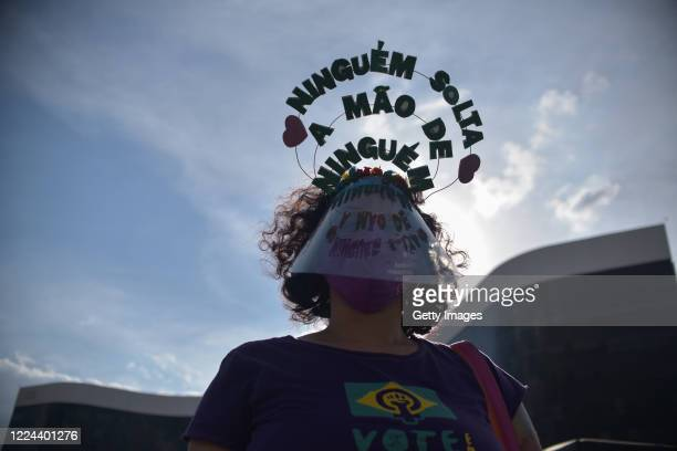 """Member of the 'Levante de Mulheres' group wearing a face shield mask and a message that reads """"no one lets go of anyone's hand"""" looks on in a rally..."""