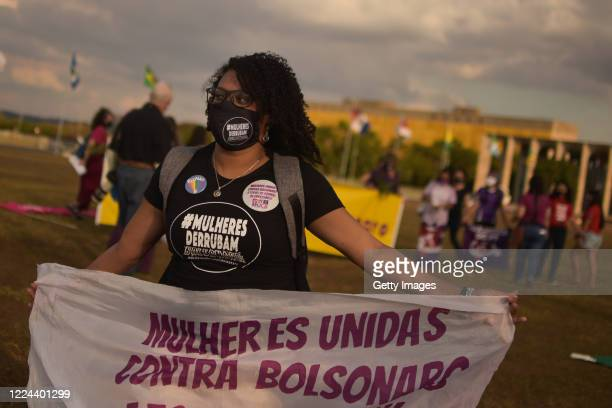 """Member of the 'Levante de Mulheres' group wearing a mask holds a sign that reads """"Women united against Bolsonaro"""" during a rally against President..."""