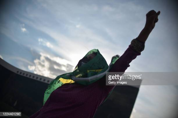 A member of the 'Levante de Mulheres' group wearing a mask raises her fist during a rally against President Jair Bolsonaro in front of the Superior...