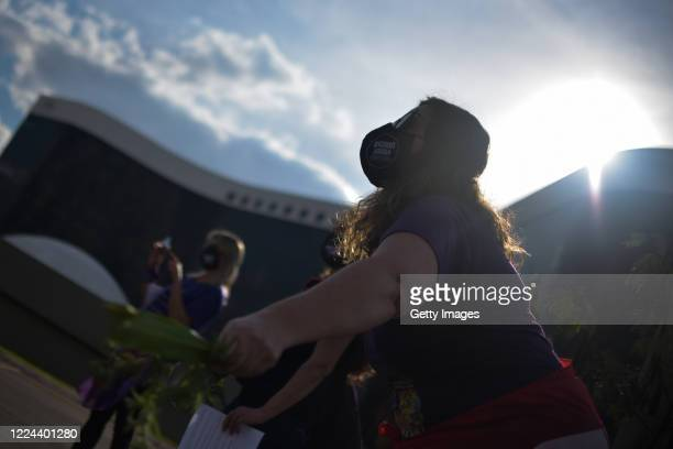 """Member of the 'Levante de Mulheres' group wearing a mask that reads """"Women bring down Bolsonaro"""" takes part of a rally against President Jair..."""